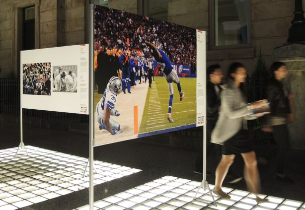 Picture taken at night. The light source is from lights in the floor. Three photographs are on display, part of a larger exhibit of winning photography from around the world. The three shown here are sports photos. The main one being a football player catching a pass.
