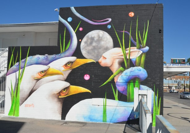 A mural by Ana Marietta in Las Vegas of three white birds with yellow beaks all looking at a figure with long rabbit ears but snake shaped body