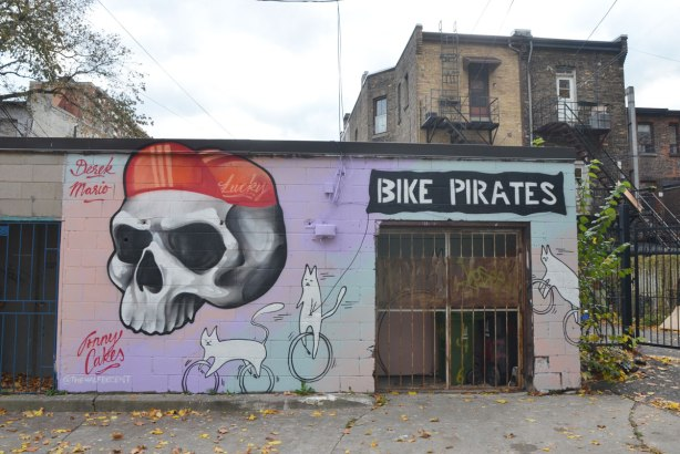 In a laneway, painted by Jonny Cakes @thehalfdecent, the wall of a workshop, shed or garage, is painted with a big skull wearing a red bike hat. Two white cats, one on a unicycle and one on a bicycle, and the words BIKE PIRATE written over the door.