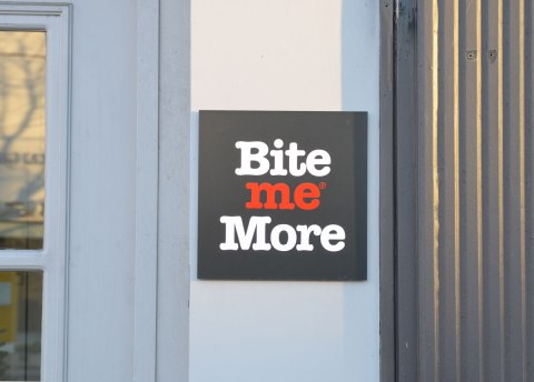 A sign on the wall outside a store that says Bite Me More