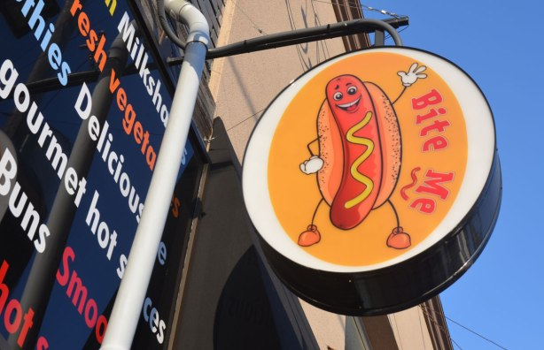 I small sign hanging over a doorway of a hot dog restaurant called Bite Me