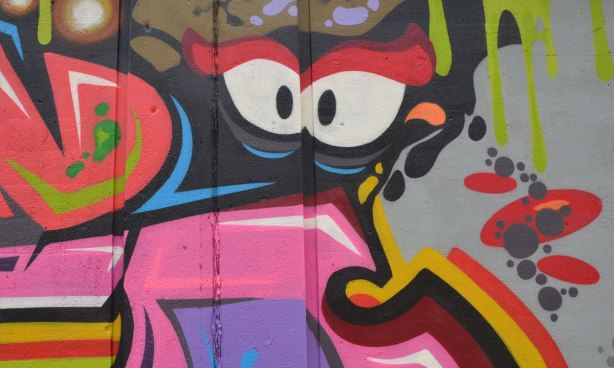 part of a larger painting on an underpass wall, eyes looking out, surrounded by many colours and shapes