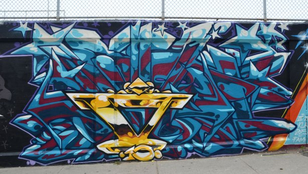 street art painting on an underpass wall. Large geometrics in dark red and blue, with a gold inverted pyramid shape