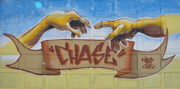 mural on a garage door, of two hands reaching for each other, in the style of Michaelangelo, with the word Chase written below on a brown banner.