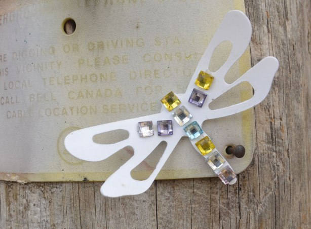 Small graffiti piece of a paper cut out dragonfly with sequins glued onto it's body and a small part of the wing.