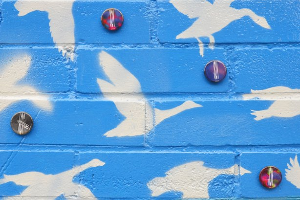White ducks or geese in silhouette flying on a bright blue sky, a close up of a mural. Amongst the birds are some buttons with the word Joy on them.