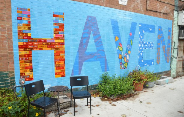 two chairs and a small table in front of a wall with a mural on it. The mural is the word Haven. Each letter is decorated in a different way.