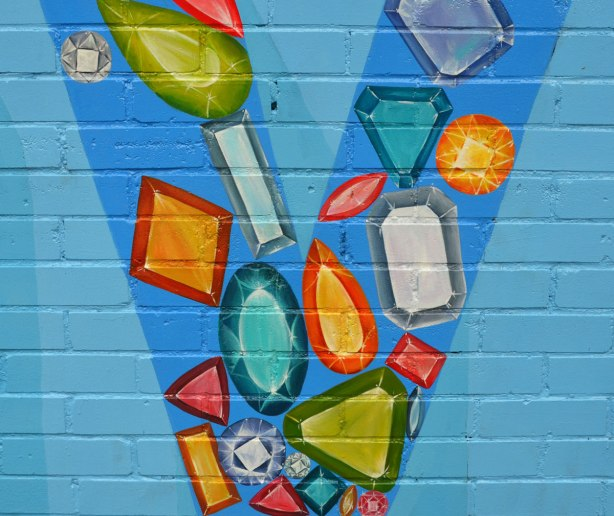 Close up of the letter V in blue on a larger mural that spells haven. Different shapes and colours of jewel stones are painted in the point of the V.