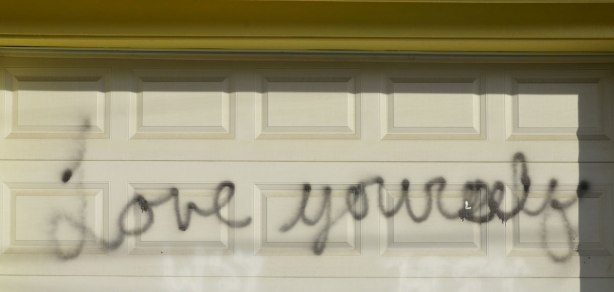 scrawled in cursive writing with black spray paint on a white garage door are the words love yourself