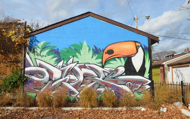 street art mural of a toucan on the side of a garage that faces a park