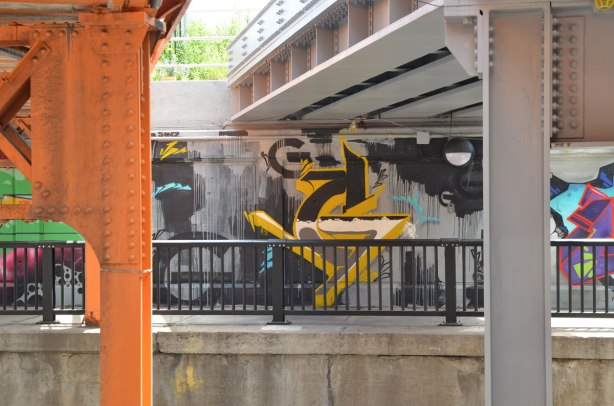 street art along the side of an underpass as seen from across the road. bridge is visible