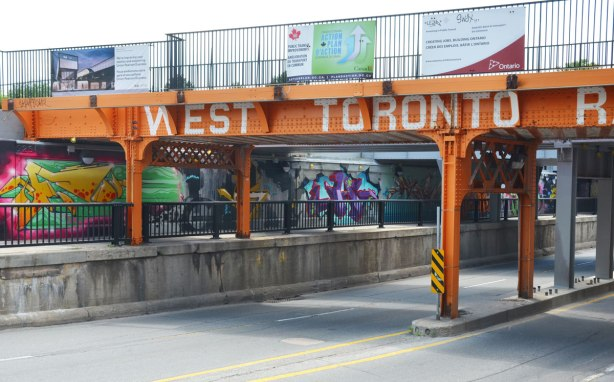 orange metal railway bridge over bloor street west, with the words West Toronto Railpath written on it in white lettes. A sidewalk runs under the bridge as well as the street. Along the side of the underpass there is a lot of street art