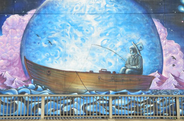 part of a larger mural, a boy is sitting at the back of a large wood boat, he is fishing, the boat is in a large bubble