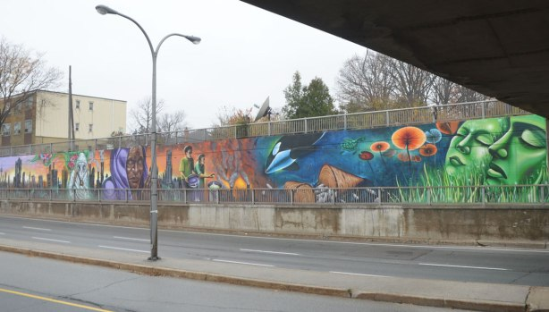 view of a mural that runs beside a sidewalk, taken from across the street