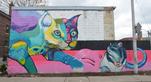 large mural of a cat chasing a mouse done in bright colours.