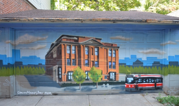 A mural on a garage door by colin makes art, showing a large brick building with a TTC streetcar passing in front of it.