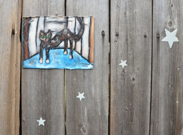 A small painting of a cat standing in a room with a light blue floor. It is mounted on a wood fence. Four glow in the dark stars are on a diagonal across the corner of the picture.