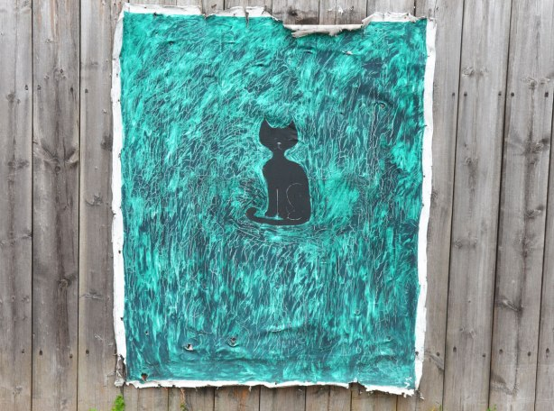 Painting on canvas stapled to a wood fence. A black silhouette of a cat that is surrounded by turquoise and farker blue swirls and smudges