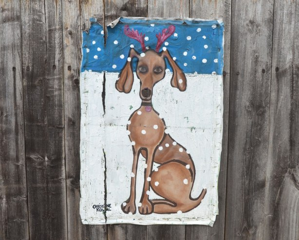 Painting on canvas stapled to a wood fence. A large dog is sitting in the snow. Red fake reindeer antlers on its head. More snow is falling from the sky.