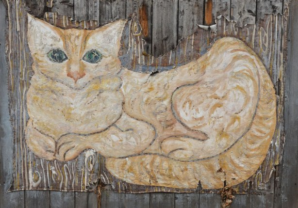 A canvas has been stapled to a wood fence, on the canvas someone has painted a large tan and white striped cat that is lounging on the ground but with its head up and alert. The canvas is wearing out a bit around the edges