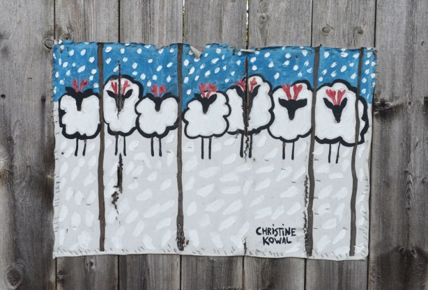 A painting of seven sheep in a line in the snow with more snow falling from the sky. The painting is on canvas and it is stapled to the fence.