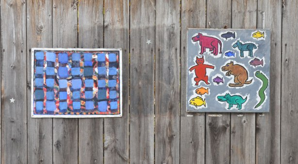Two paintings on a wood fence. One is a collection of animals in bright colours and the other is an abstract with a large amount of blue in it.