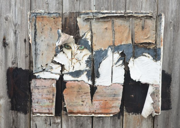 A very weathered painting of a cat on canvas and stapled to a wood fence. The canvas has started to rip vertically in places. The pattern of the rips sort of matched the pattern of the boards in the fence.