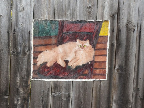 Painting on canvas stapled to a wood fence. A long haired light brown cat resting on a striped carpet or blanket