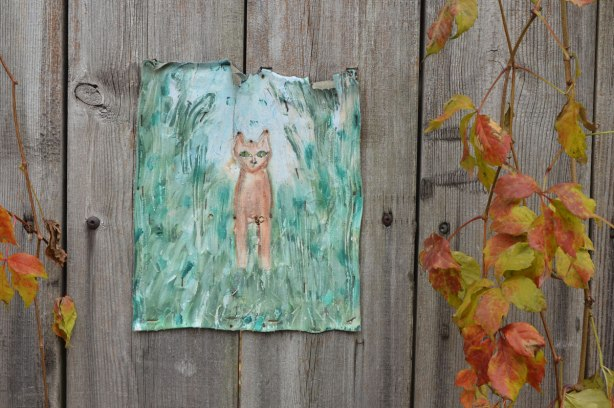Painting on canvas stapled to a wood fence. A small brown cat in amongst tall grass. A vine is growing on the fence beside the picture.