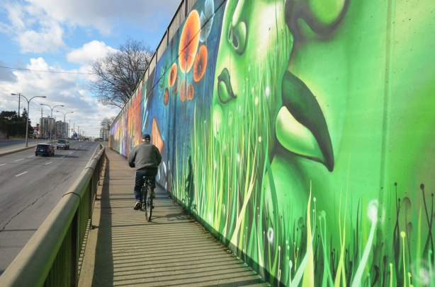 a man cycles past a large mural, two very large green faces are in the foreground