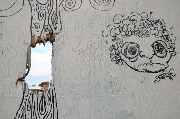black line drawing on white fence with a hole in it. On a plywood fence, a face, and a lot of spirals