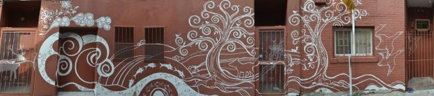 panorama picture of mural by Monica on the Moon, white line drawings on brown background, across the back of a building in a laneway