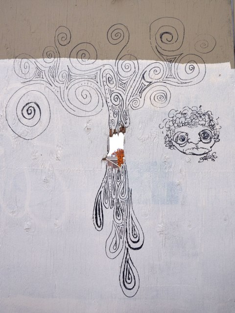 black line drawing on white fence with a hole in it. A face, and a lot of spirals