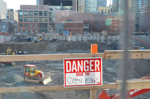 red and white danger sign on a makeshift wooden fence that says danger due to open edge. Beyond it is a very large hole for a construction site. A bulldozer is in the hole, downtown Toronto is in the background.