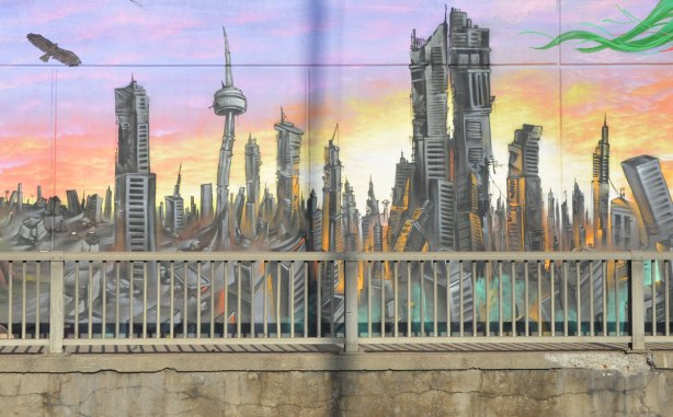 part of a mural by Essencia Art Collective on Lawrence West in Toronto showing the drastic possible environmental effects of not looking after the planet - a black and crumbling city with the CN Tower looking like it's about to fall down