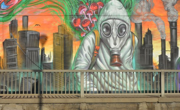 part of a mural by Essencia Art Collective on Lawrence West in Toronto showing the drastic possible environmental effects of not looking after the planet - a person covered in a grey suit and wearing a gas mask in front of a decaying and falling down city
