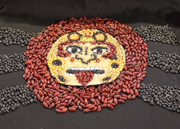 a face shape made of dried beans and corn. red beans make a circle around the face, black beans make 6 rays coming out from the circle. The face is corn with bean features.