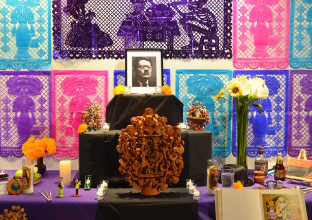 elaborate and colourful ofrenda with purple, blue and pink paper cut outs on the wall behind.