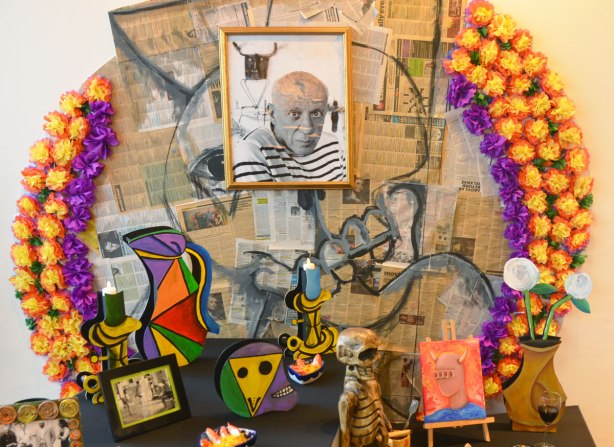 An ofrenda, or altar, in the memory of Pablo Picasso at a day of the dead festival. There is a photo of him surrounded by different objects and symbols representing his life and things that he did