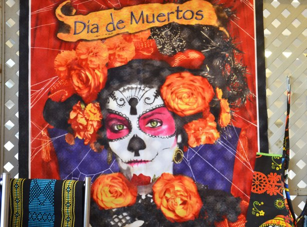 fabric hanging on a wall. There is a picture on the fabric of a woman's face painted white to look like a skull but with pink around the eys. Many orange roses surround her face