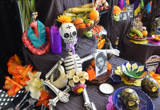 objects on an ofrenda at a day of the dead celebration, decorated skulls, a small skeleton, some old photos of people, flowers, fruit,
