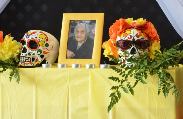 an ofrenda with a picture of a woman in a frame sitting on a table. One each side of her is an elaborately decorated skull. One of the skulls is wearing sunglasses and a wreath of yellow and orange flowers around the top of its head.
