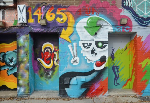 doorways behind 1465 Gerrard St. covered with street art, a white ghostly skull and a girl standing with her head back and arms upraised