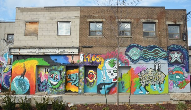 The back of a few two storey shops where the bottom half is covered with street art and murals
