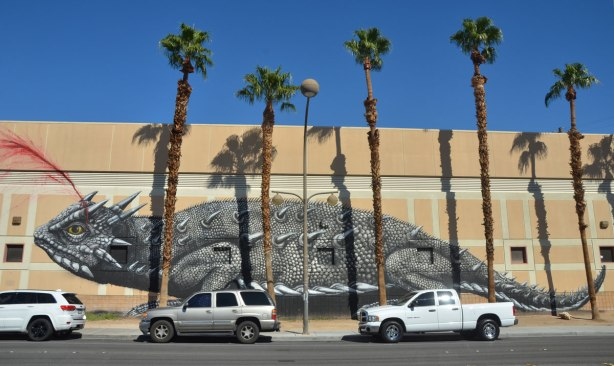 A very large grey tone (black and white) realistic painting of an iguana on the side of a building. Tall palm trees are in front of it as are three vehicles parked on the street. The iguana is shooting red blood from one of its eyes.