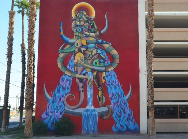 A large creature mural, yellow and orange halo around its head, blue furry legs, 5 storeys high, red background.