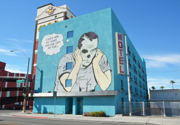 "large mural on the side of a turquoise coloured motel, about 5 storeys high. A man is sitting with his elbows on the table, head in hands, empty glass in front of him. Thought bubble says ""I gave her my heart and she left me for...."" One of the man's eyes seems to be missing."