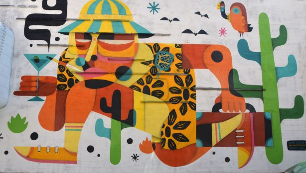 A colourful mural by Reuben Sanchez and a stylized man running through the desert, wearing a yellow and green striped hat, an orange shirt with black flowers on it, holding a martini glass and smoking a cigarette. He's wearing shorts and yellow socks