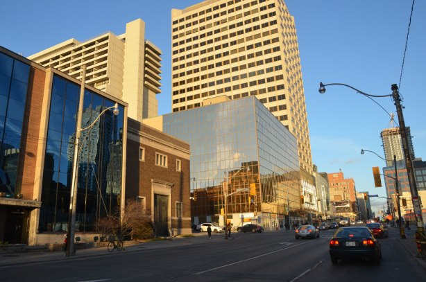 looking east along Eglinton Avenue towards Yonge street with Duplex Ave in the foreground. The old Toronto Hydro-Electric building is in the picture, with a newer structure with a glass front beside it. New buildings between Duplex and Yonge on the north side of Eglinton are also in the picture.