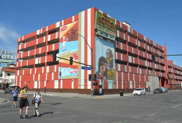 The El Cortez hotel parking structure on a corner in downtown Las Vegas. It is painted mostly in rust colour but with some white and tan stripes. There are two large murals where the corner meets.